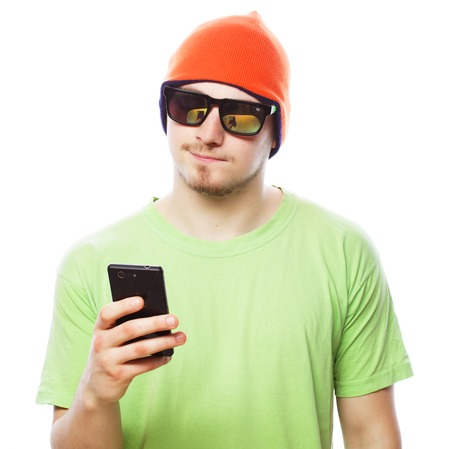 tehnology: life style, tehnology and people concept: cheerful man in green shirt and bright hat using smartphone, isolated on white Stock Photo