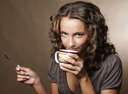 people drinking coffee: young pretty woman drinking coffee Stock Photo