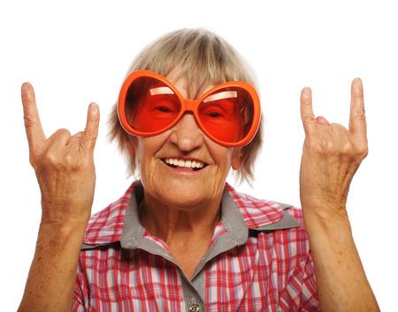 gente loca: Mujer mayor que lleva grandes gafas de sol que hacen la acción cobarde aislados sobre fondo blanco