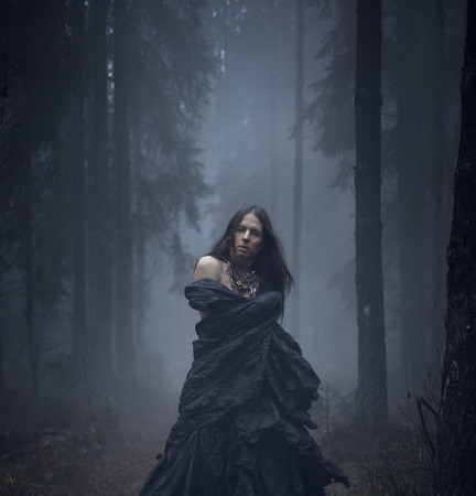 dark elf: Romantic young man with long hair in the dark forest