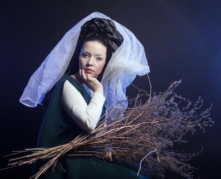 medieval dress: chica en traje medieval con mont�n de palos en el humo