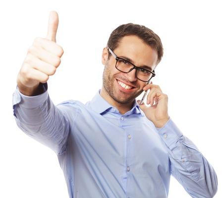 gente feliz: estilo de vida, los negocios y la gente concepto: hombre joven ocasional que muestran los pulgares para arriba signo, mientras habla por teléfono y sonriendo a la cámara. Aislado en el fondo blanco