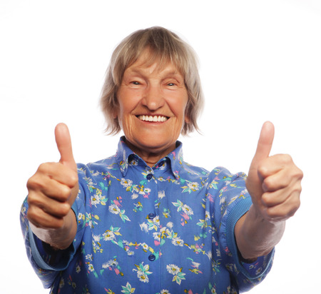 Old happy woman showing ok sign on a white background