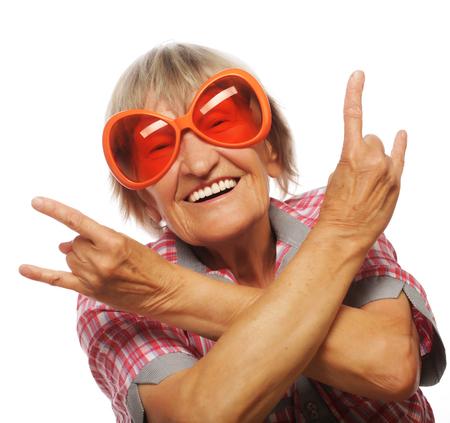 adulto mayor feliz: Mujer mayor que lleva grandes gafas de sol que hacen la acción cobarde aislados sobre fondo blanco