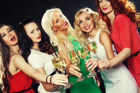 clinking: Grupo de chicas de fiesta tintinean flautas con vino espumoso
