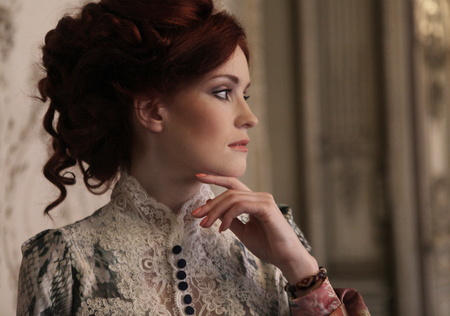 Hermosa mujer joven de pie en la sala de palacio.