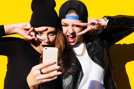 estilo urbano: Dos amigos de muchachas adolescentes en traje de última moda al aire libre hacen selfie en un teléfono.