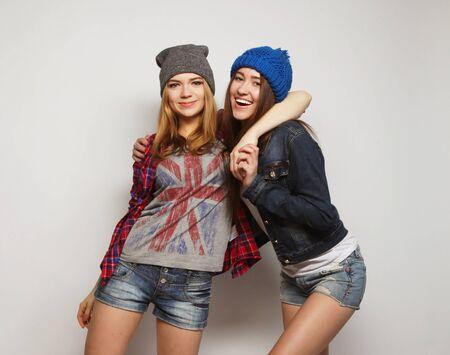 swag: Retrato de dos elegantes pastrulitas sexy mejores amigos, vistiendo trajes lindo bot�n y sombreros. Durante backround gris.