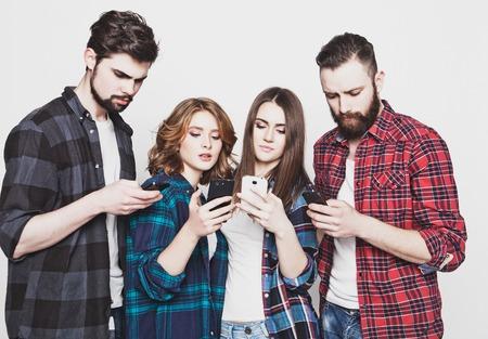 technologie en internet concept: groep jonge mensen te kijken naar hun smartphones