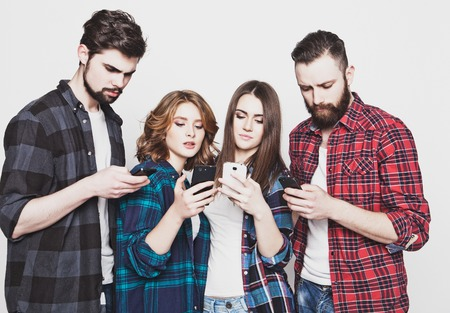 technology and internet concept:group of young people  looking at their smartphones
