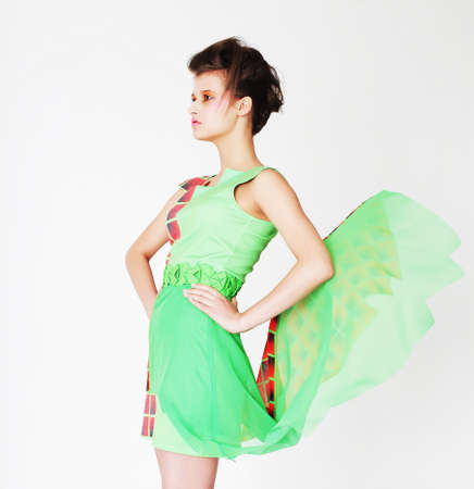 dress blowing in the wind: Fashion model in bright green dress over white background