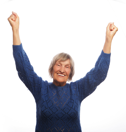 senior happy woman gesturing victory over white background