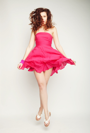womanliness: Young charming female in pink chiffon dress jumping over grey background