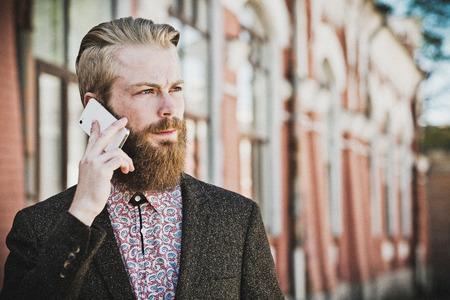 hombre con barba: Young bearded man with mobile, outdoor, summer time Foto de archivo