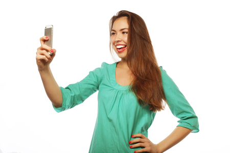 tehnology: People, lifestyle and tehnology concept: pretty teen girl wearing green shirt, taking selfies with her smart phone -  isolated on white