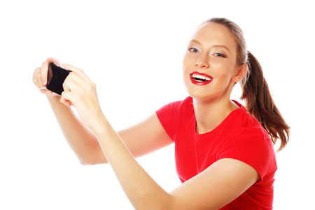 tehnology: People, lifestyle and tehnology concept: pretty woman taking selfies with her smart phone - isolated on white