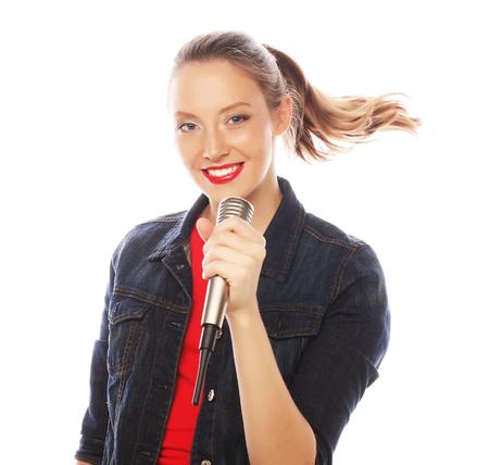cantando: Chica cantante feliz. Mujer de la belleza con camiseta roja con micrófono sobre fondo blanco.