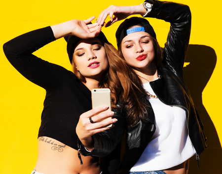 Two teenage girls friends in hipster outfit outdoors make selfie on a phone. Banque d'images