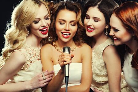 cantando: Cuatro hermosas chicas con estilo cantando karaoke en el club Foto de archivo