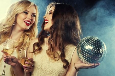 felicity: two beautiful young women with wine glasses and disco ball. Stock Photo