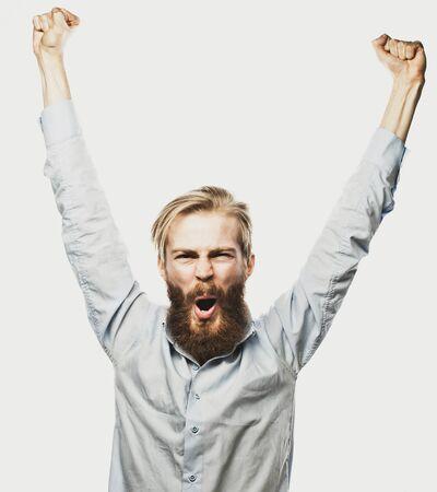 loteria: estilo de vida, la felicidad y la gente concepto: hombre joven con barba positividad mostrando la mano de pie contra el fondo gris. Foto de archivo