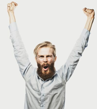 lottery: life style, happiness and people concept: young positivity  bearded man showing hand up standing against grey background.