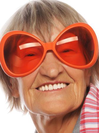 seniority: Senior woman wearing big sunglasses doing funky action isolated on white background Stock Photo
