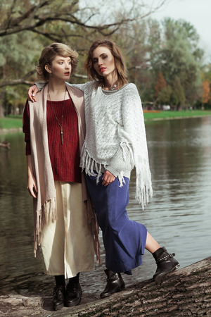 two persons only: photo of a two beautiful women posing on a tree near lake. Stock Photo