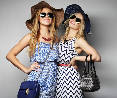 fashion concept: two sexy young women in summer fashion dress and straw hats, studio background
