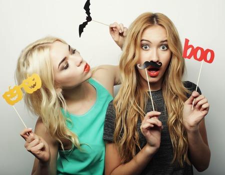 amicizia: due eleganti sexy vita bassa ragazze migliori amici pronti per il partito, su sfondo grigio