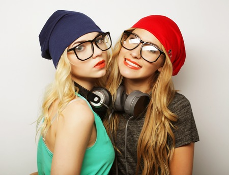 babes: Studio lifestyle portrait of two best friends hipster girls wearing stylish bright outfits, hats, denim shorts and glasses, going crazy and having great time together. Young and beauty. Stock Photo