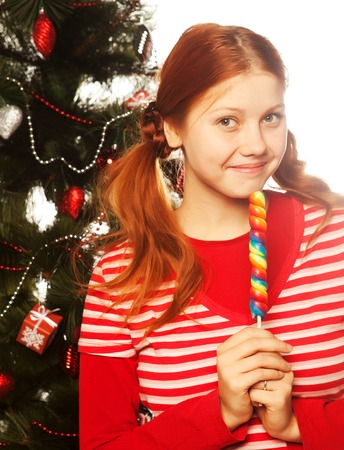lolly pop: Pretty young redhair woman  holding lolly pop. Christmas tree.