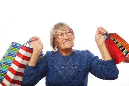 80 90: Happy senior woman with shopping bags isolated on white