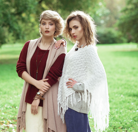 two persons only: Autumn. Photo of a two beautiful women in the park.