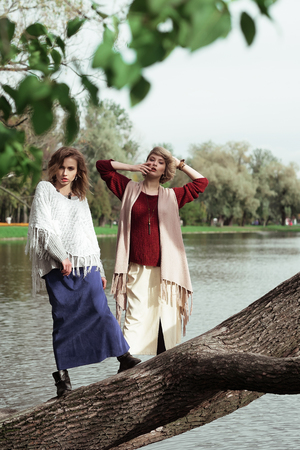 2 persons only: photo of a two beautiful women posing on a tree near lake. Stock Photo
