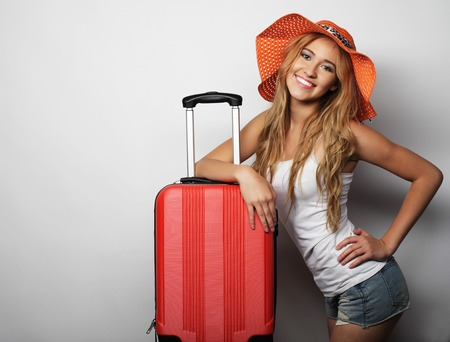 young teen girl nude: Portrait of  young woman wearing big straw orange hat  standing with orange travel bag Stock Photo