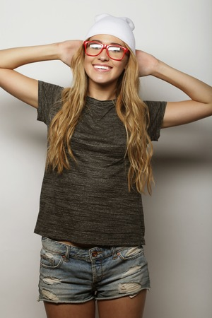 clothing model: Fashion studio portrait of pretty young hipster blonde woman with glasses , wearing stylish urban t shirt and hat, over white background