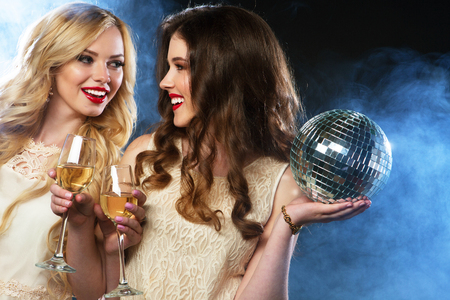 girl party: two beautiful young women with wine glasses and disco ball. Stock Photo