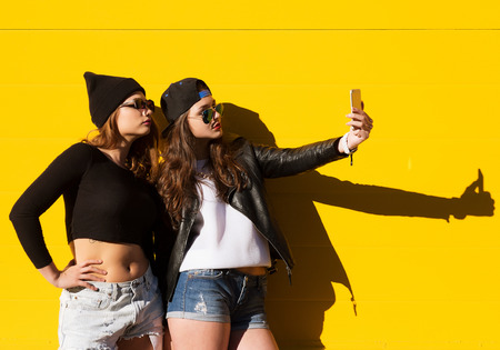 Two teenage girls friends in hipster outfit outdoors make selfie on a phone. Stock Photo