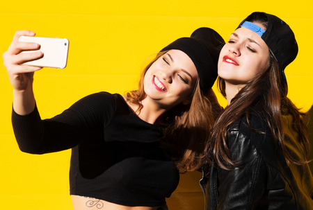 brunette teen: Two teenage girls friends in hipster outfit outdoors make selfie on a phone. Stock Photo
