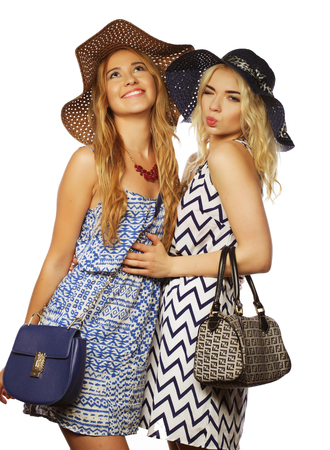 Studio lifestyle portrait of two best friends  girls wearing stylish summer dress and straw hats,  having great time together. Isolated on white.