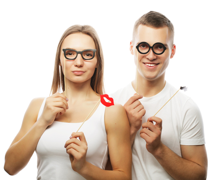 flirtation: people, party, love and leisure concept - lovely couple holding party glasses and mustaches on sticks, over white  background