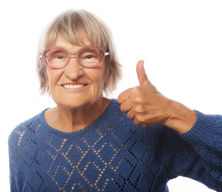 80 90: Old happy woman showing ok sign on a white background