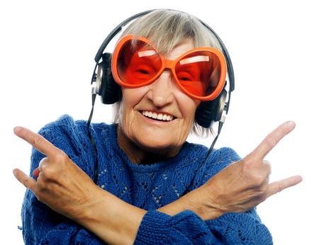Funny oude dame luisteren muziek en het tonen van duimen omhoog. Geïsoleerd op wit. Stockfoto