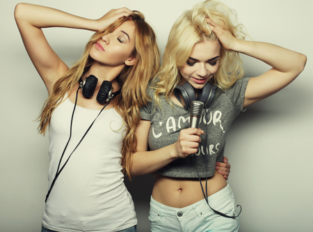 happy girls: life style, happiness, emotional and people concept: beauty hipster girls with a microphone singing and having fun Stock Photo