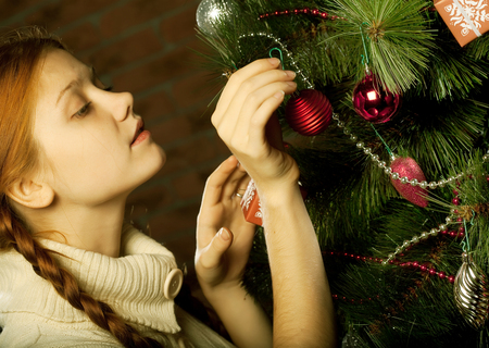 decorar: girl decorate the Christmas tree in a house interior