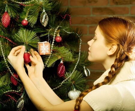 decorate: girl decorate the Christmas tree in a house interior