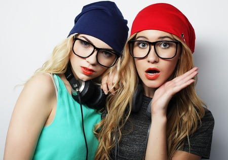 going crazy: Studio lifestyle portrait of two best friends hipster girls wearing stylish bright outfits, hats, denim shorts and glasses, going crazy and having great time together. Young and beauty. Stock Photo