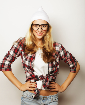 going crazy: Young hipster girl having fun and going crazy, wearing glasses hat and bright make up. White  background.