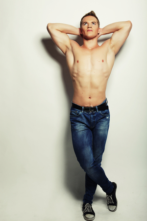 muscular body: Sexy fashion portrait of a hot male model in stylish jeans with muscular body posing